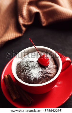 Chocolate cake in a red mug with a cherry on a wooden background, close up - stock photo