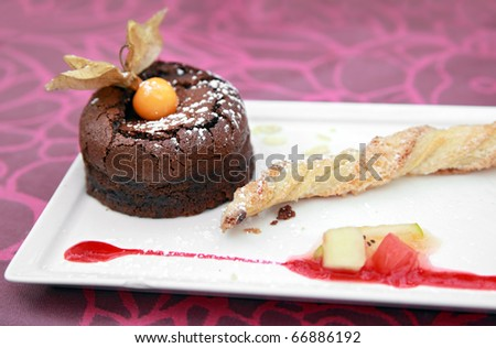 """Chocolate cake - individual portion of chocolate """"fondant"""" cake served with puff pastry and fruit - stock photo"""