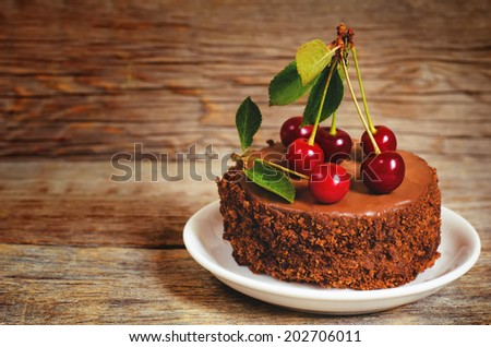 chocolate cake mini with cherries on a dark wood background. toning. selective focus on the cherry on the cake - stock photo