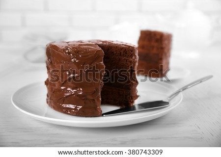 Chocolate cake on plate with a cut piece on unfocused background