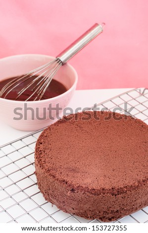 Chocolate cake on sieve and chocolate batter preparation with whisk. - stock photo