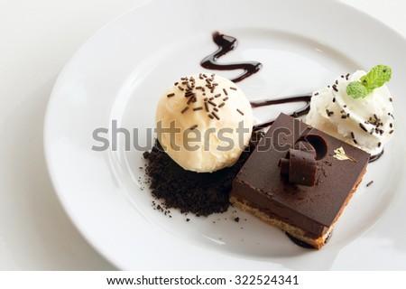 Chocolate cake serve with vanila ice cream and whipped cream. - stock photo