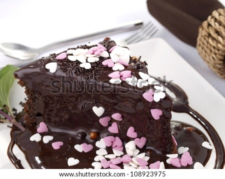 Chocolate cake served with mint leaves. - stock photo