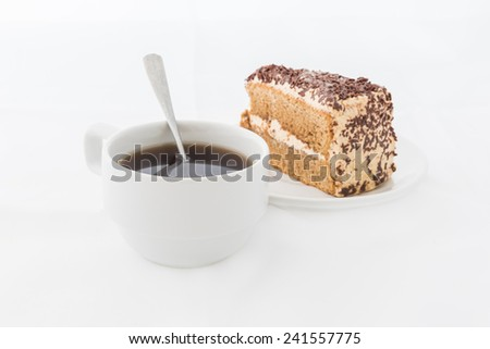 Chocolate cake slice with curl on white dish with hot drink. white background - stock photo