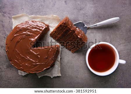 Chocolate cake with a cut piece and blade and cup of tea on gray background, closeup - stock photo