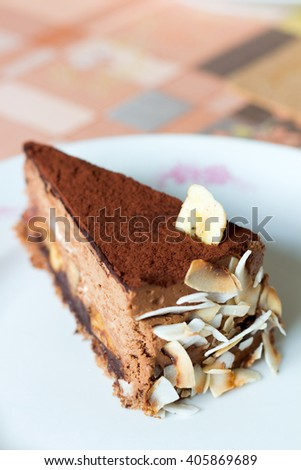 Chocolate cake with almond nuts on an white plate, top view - stock photo
