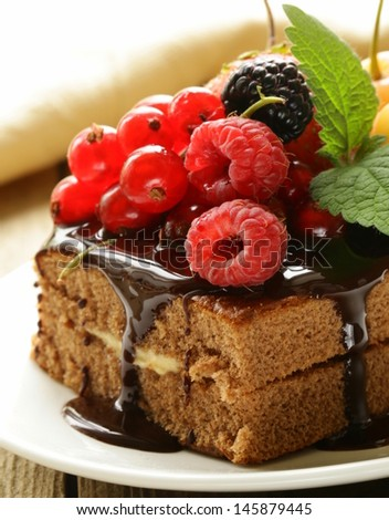 chocolate cake with berries (raspberry, currant, cherry) and chocolate sauce - stock photo