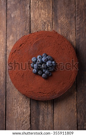 Chocolate cake with cacao powder and blueberries on a wooden background. top view