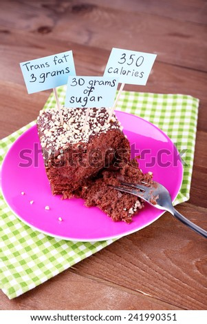 Chocolate cake with calories count labels and fork on color plate and napkin, on wooden table background - stock photo