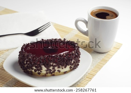 Chocolate cake with cherry jelly and cup of hot coffee on bamboo napkin - stock photo