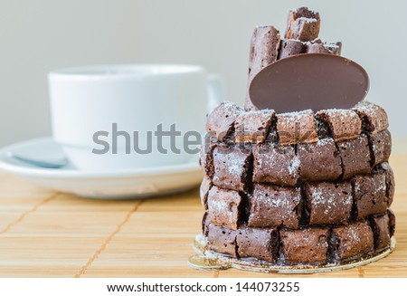 Chocolate cake with choco stick roll on the bamboo table with white tea cup&tea pot