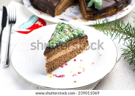 Chocolate cake with chocolate butter cream filling and dark chocolate glaze decorated with green frosting and confetti for Christmas or birthday on white plate (Prague chocolate cake) - stock photo