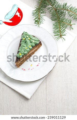 Chocolate cake with chocolate butter cream filling and dark chocolate glaze decorated with green frosting and confetti for Christmas on white plate (Prague chocolate cake). Above with copy space - stock photo