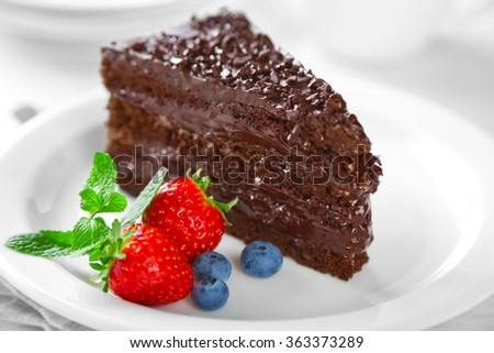 Chocolate cake with chocolate cream and fresh berries on plate, on light background