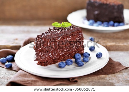 Chocolate cake with chocolate cream and fresh blueberries on plate, on wooden background - stock photo