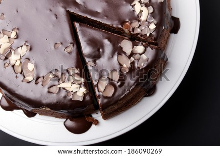 Chocolate cake with chocolate frosting on black background, top view - stock photo