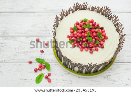 Chocolate cake with cream and cranberries on wooden background - stock photo