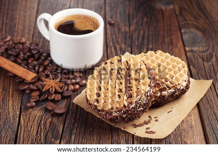 Chocolate cake with cream and cup of hot coffee on dark wooden table - stock photo