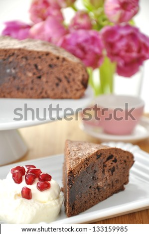 Chocolate Cake with cream and tulips in the background