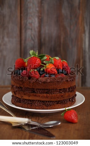 Chocolate cake with icing and fresh berry on wooden background - stock photo