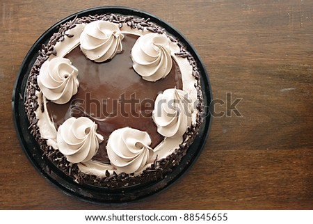 Chocolate cake with mocha icing swirls on an antique table - stock photo