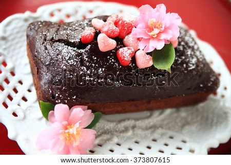Chocolate cake with powdered sugar, heart-shaped candies and fresh flowers - stock photo