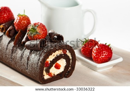 Chocolate cake with strawberries and cream on wooden board - stock photo