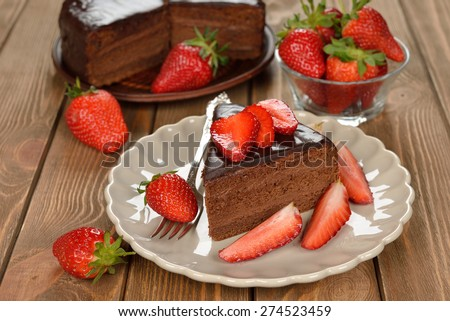 Chocolate cake with strawberries on a brown background - stock photo
