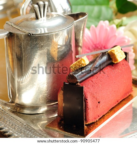 Chocolate cake with tea-pot and flower