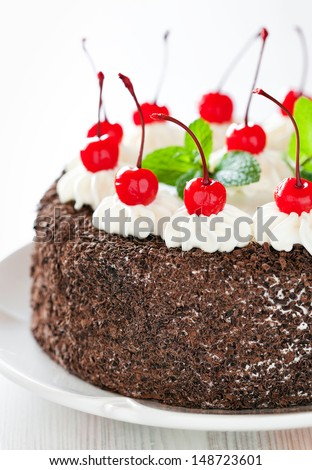 Chocolate cake with whipped cream and glazed cherries, selective focus - stock photo
