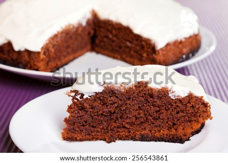 Chocolate cake with white cream, from above with one piece cut from the whole cake
