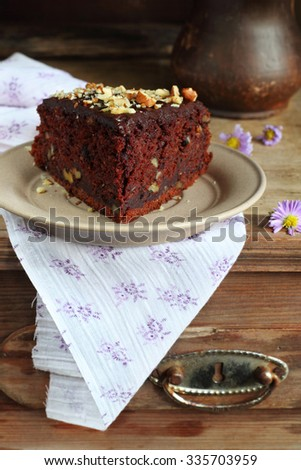 Chocolate cake with zucchini and walnuts on a saucer on a wooden box.