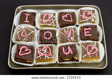 Chocolate cakes with 'I love you' and 'love hearts' written in icing.