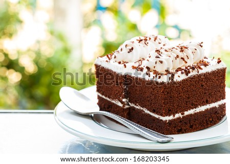 chocolate cakes with white cream on top and spoon on plate and bokeh at background - stock photo