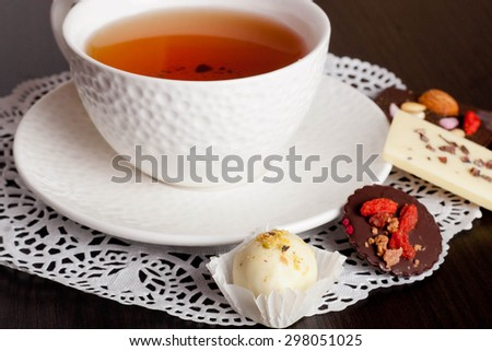 Chocolate candies and cup of tea, horizontal, close up - stock photo