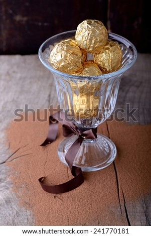 Chocolate candies assortment in glass bowl on wooden background. Selective focus - stock photo