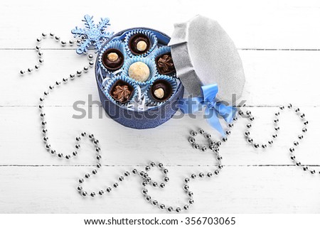 Chocolate candies in a gift box with a bow on a light wooden background - stock photo