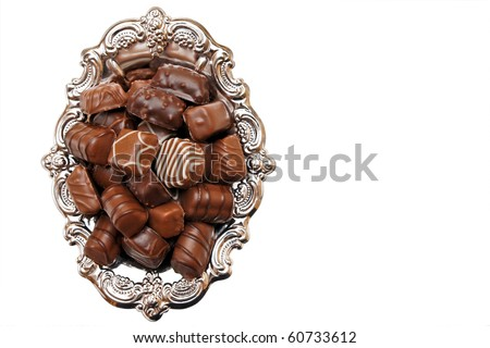 Chocolate candies on a silver platter isolated on white background.. You can write text on the right side.