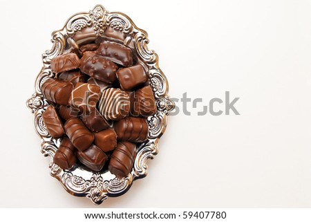 Chocolate candies on a silver platter. You can write text on the right side. - stock photo