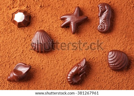 Chocolate candies on sea subjects on background of cocoa powder - stock photo