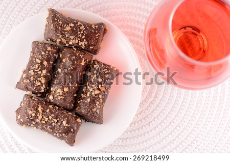 chocolate candies on white plate and red wine in glass - stock photo