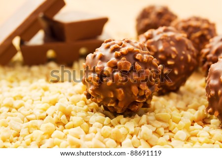 Chocolate candy balls with chopped nuts and chocolate bars