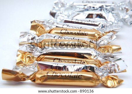 Chocolate Candy Bars in Silver and Gold Wrappers - stock photo