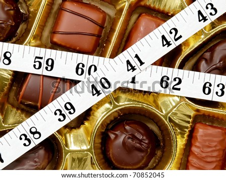 chocolate candy box wrapped in a tape measure - concept of high calorie diet saboteurs - stock photo