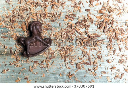 Chocolate candy in the shape of a horse on the background pieces of chocolate. Shallow DOF. Flat lay - stock photo