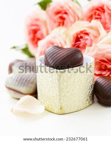chocolate candy in the shape of hearts and pink roses for Valentine's day holiday - stock photo