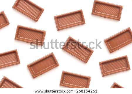 chocolate candy pieces background on white - stock photo