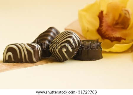 chocolate candy with yellow orchid - stock photo