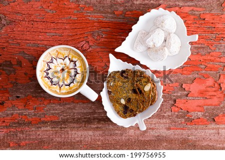 Chocolate caramel latte with an artistic pattern in the froth served with walnut crisp bread and sugar-coated almond wedge cookies, overhead view on a grungy red wood background - stock photo