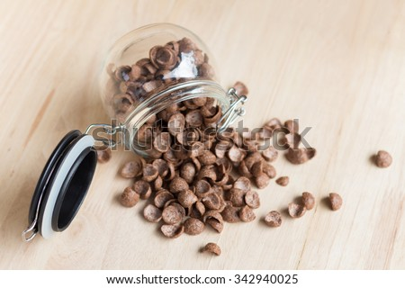 Chocolate cereal cornflakes spilling out from the glass jar(selective focus on the jar) - stock photo